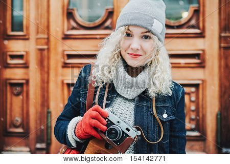 Young blond curly female tourist in warm clothes with old film camera and city map standing on the background of wooden doors winter snow