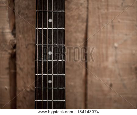 Fingerboard From The Acoustic Guitar On Wooden Background