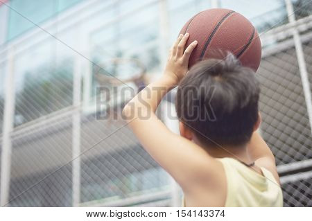 Rear View Of Boy Aiming Basketball Hoop Before Shooting