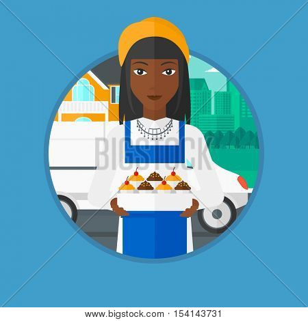 An african-american female baker holding a box of cupcakes on the background of delivery truck. Young baker delivering cakes. Vector flat design illustration in the circle isolated on background.