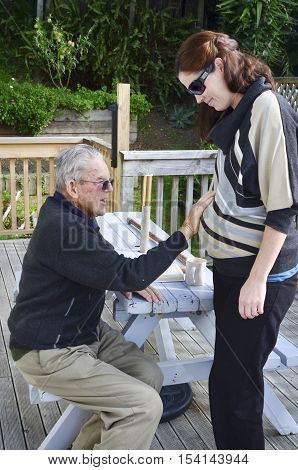 Grandfather (95 years old) holds his pregnant granddaughter (30) abdomen. Concept photo of pregnancy pregnant woman family lifestyle.