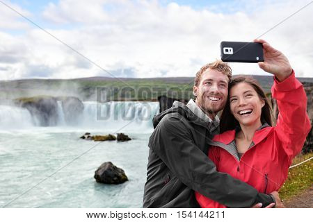 Selfie couple taking smartphone picture of Godafoss waterfall outdoors on Iceland. Couple visiting famous tourist attractions and landmarks in Icelandic nature landscape. Mixed race couple having fun.