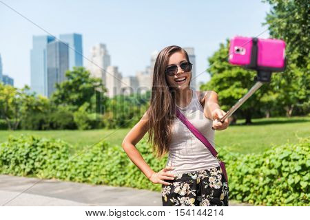 Happy travel tourist taking self-portrait picture with mobile phone and selfie stick at popular attraction in NYC. Central park woman walking in summer park in New York City, Manhattan, USA.