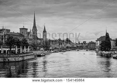 View of historic Zurich city center with Fraumunster Church Munsterbrucke bridge and Limmat river on a cloudy rainy day Zurich Switzerland. Black and white photography.