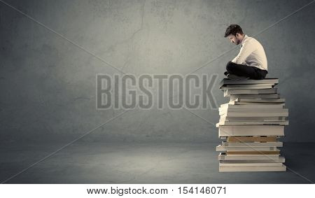 A serious student in elegant suit sitting on a stack of books in front of dark grey background