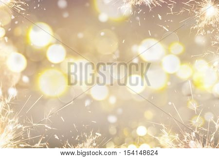 Christmas glowing Golden Background. Christmas lights. Gold Holiday New year Abstract Glitter Defocused Background With Blinking Stars and sparks. Blurred Bokeh