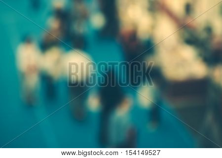 Abstract blurred people attending event in exhibition hall press conference or celebration party visitors of indoor fair or other commercial happening retro toned image.