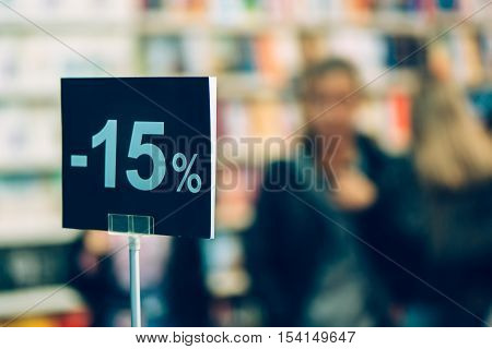 Fifteen percent discount in bookstore blur customers in background searching for a book to buy