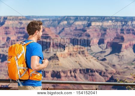 Grand Canyon hiking tourist man with backpack bag looking at viewpoint lookout on Grand Canyon, Arizona, USA. People hiking in Grand Canyon enjoying view of nature landscape wearing backpack.