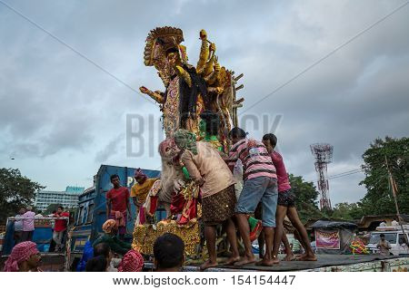 KOLKATA, INDIA - OCTOBER 10, 2016: Durga idol being brought down from a truck by group of workers for immersion in the Ganges river. The immersion marks the end of the five day long Durga puja.