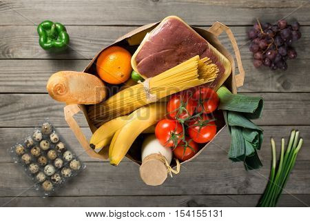 Full paper bag of groceries on wooden background top view