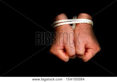 Hands of a missing kidnapped abused hostage victim man tied up with rope in emotional stress and pain afraid restricted trapped call for help struggle terrified locked in a cage cell.
