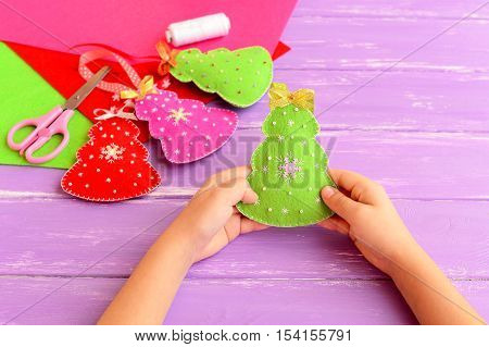 Child holding Christmas tree toy in his hands. Child showing Christmas crafts. Felt crafts ideas for kids. Scissors, thread, needle on lilac wooden background