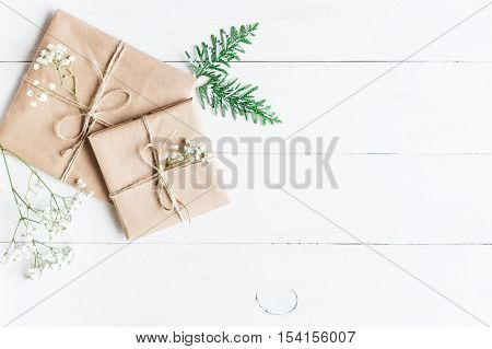 Christmas composition. Christmas gift thuja branches and gypsophila flowers. Top view flat lay
