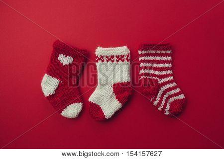 Mini Christmas Stockings.Three red and white wool Christmas stockings on red background.