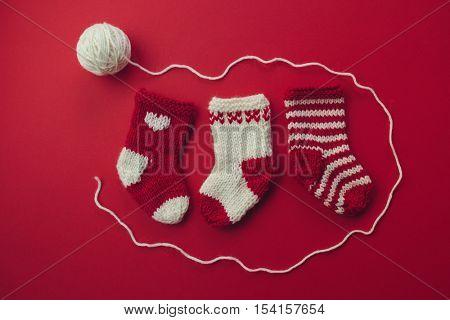 Mini Christmas Stockings.Three red and white wool Christmas stockings side by side.