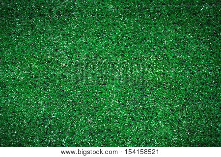 Top view of artificial green grass texture for golf course background and soccer field in vignette with copy space for text or image. Dark edged.