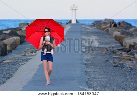 Young mother carries her infant baby and red umbrella in Seaway Gold Coast Australia.