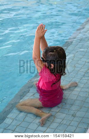 Child practices her stroke during swimming pool lesson.