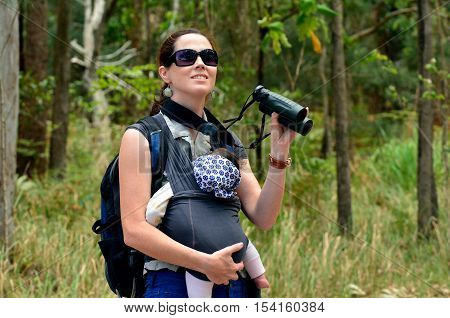 Mother hike outdoor with her infant baby in the nature .