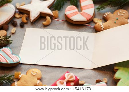 Empty greeting card in gingerbread cookies frame. Free space on white card surrounded by traditional Christmas cookies. Holiday, winter, celebration, new year concept