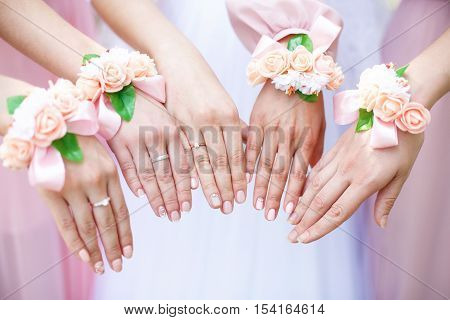 Bride and bridesmaids with flower bracelets on hands. Close-up