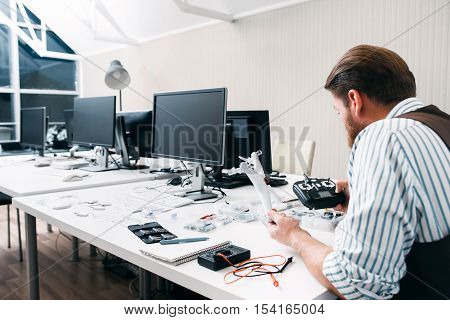 Office worker sitting late at work with drone. Excited of new electronic toy man. Hobby, leisure, entertainment, enthusiasm, passion concept