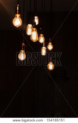 Incandescent lamps in a modern loft. Edison lamp composition on dark background, free space for text or advertisement. Teamwork, idea, creativity, light concept