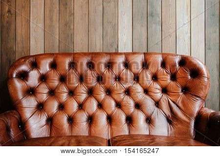 Old leather sofa on wooden background, void. Shabby used luxury furniture, free space on plank wall