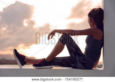 Fitness athlete sports woman relaxing after workout sitting on window looking at sunset view. Silhouette of runner in activewear resting at home on outdoor terrace in sky background.
