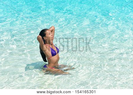 Beach sexy woman in bikini swimming in perfect crystalline blue water ocean. Beautiful Asian girl sun tanning and relaxing in tropical sea taking care of her hair and skin.