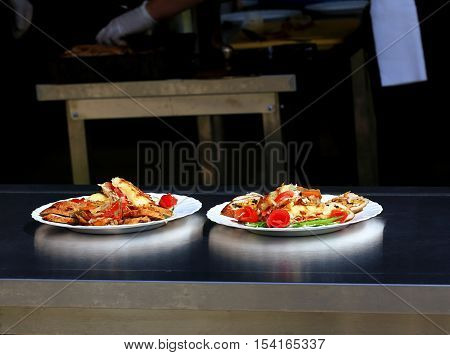 Two plates with meat dish and garnish