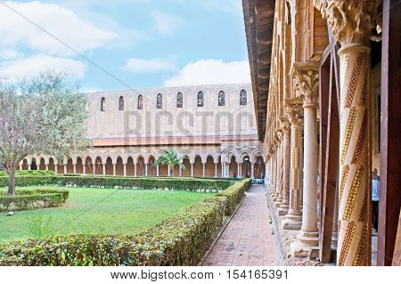 MONREALE ITALY - OCTOBER 10 2016: The garden in courtyard of Monreale Cathedral surrounded by shady gallery with scenic stone columns decorated with carvings mosaics and inlay on October 10 in Monreale.