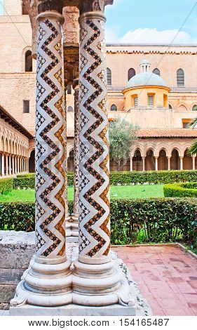 The white stone columns in garden of Monreale Cathedral decorated with zigzag inlay consisting of small mosaic stars Sicily Italy.