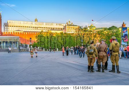 MOSCOW RUSSIA - MAY 10 2015: The people in Second World War Soviet soldiers uniform at the Kremlin Wall during Victory Day celebration on May 10 in Moscow.