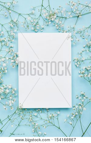 Wedding mockup with white paper list and flowers gypsophila on blue background from above. Beautiful floral pattern. Flat lay style.