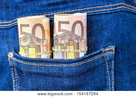 Blue jeans pocket with rolls of fifty euro notes