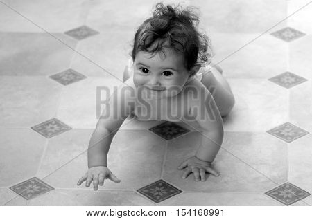 Little baby (girl age 07 months) crawling on the floor. concept photo child development (BW)
