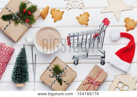 Cup of hot cocoa, holiday decorations, gift or present, miniature fir tree and shopping basket. Christmas or winter planning concept. Flat lay style.