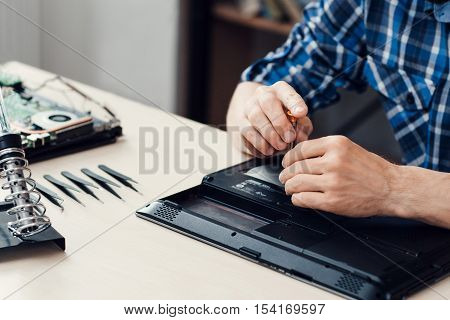 Laptop disassembling in repair shop, close-up. Engineer hands unscrewing computer part in repair shop