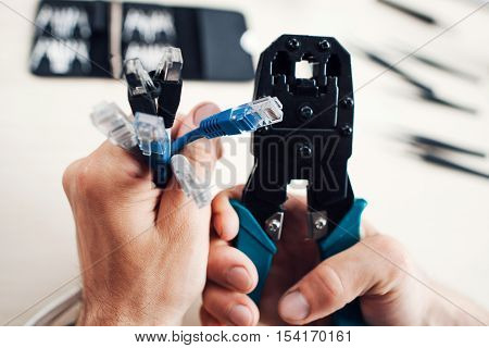 Hands holding rj45 cables and forceps for crimping modular plug. Network development, telecommunications, business concept