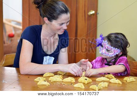 Jewish Mother and her child (daughter girl age 5) in costume preparing and cooking togather home made Hamantaschen cookie on Purim Jewish Holiday.