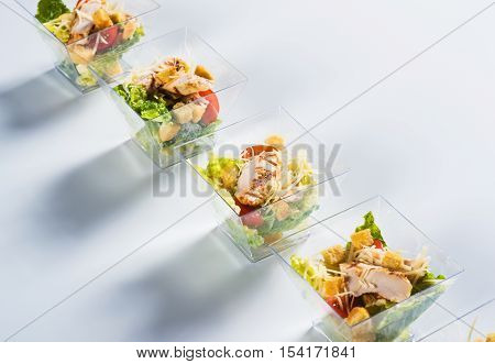 Salad with chicken and crackers in glass on light background