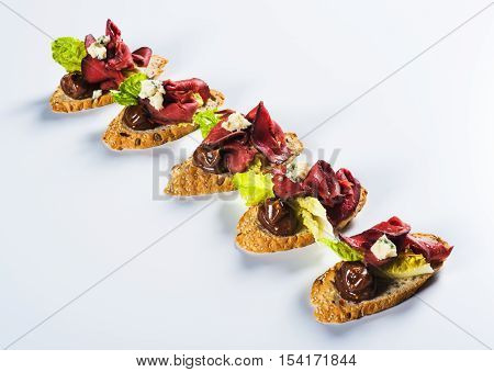 Bruschettas with beef and cheese on light background