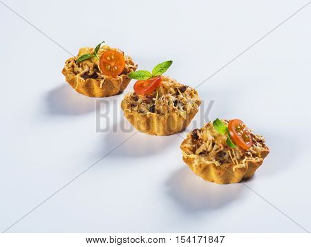 Tartlet with mushrooms and cheese on light background