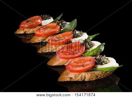 Bruschetta with mozzarella tomato and pesto on black background