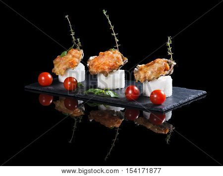 Beautifully decorated baked oyster with cheese on plate on black background
