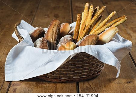 Bread in old wicker basket on wooden background