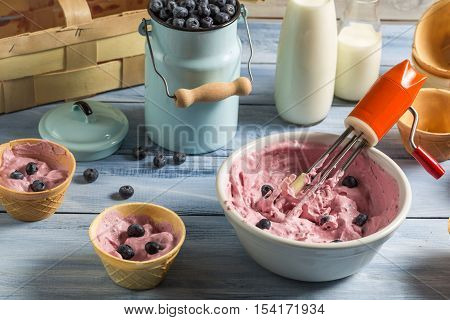 Preparing homemade fruit ice cream on old wooden table