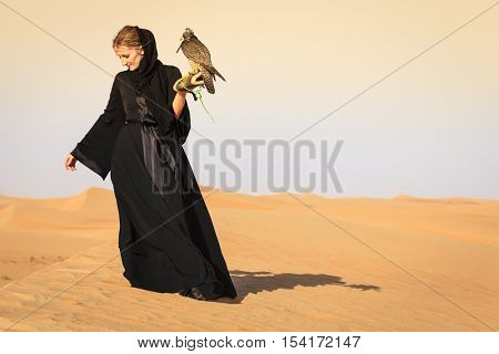 Young woman in abaya with Peregrine Falcon in Dubai Desert Conservation Reserve, UAE